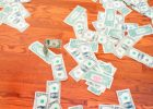 A trail of cash on a wooden floor.