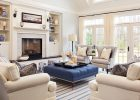 blue tufted ottoman coffee table in living room with strips carpet and white sofas