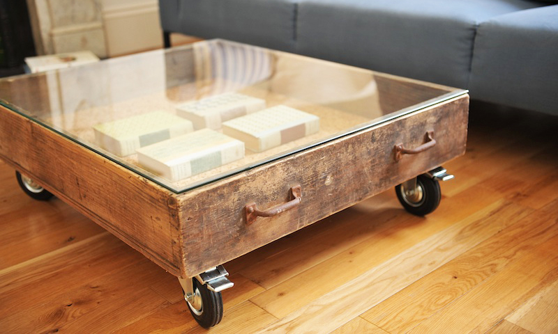 metal-rectangle-coffee-table-with-wheels-glass-on-top-table-with-vinyl-flooring-and-blue-fabric-sofa