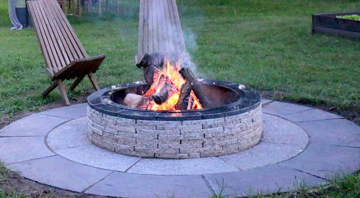 outdoor wood fire pit-with-paving-stones-and-flames
